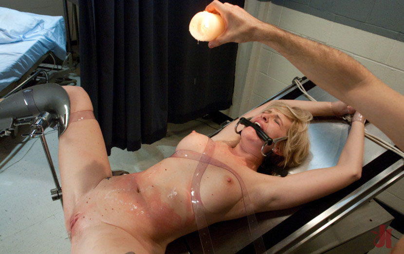 Bound and gagged blonde has wax covering her body while her doctor watches