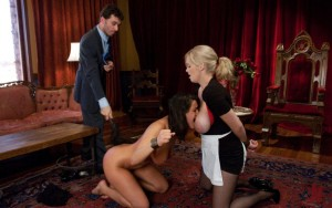 Cuffed slave is flogged by her Master and forced to lick the maid's tits