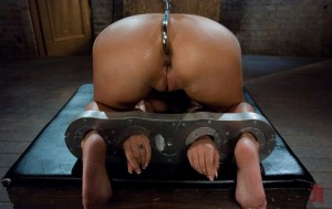 Brunette girl is bound with cuffs while having an anal hook inserted