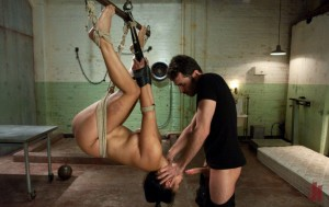 Upside-down suspended brunette slut gets her throat fucked