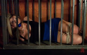Blonde slave is tied up with her hands behind her back and gagged in a cage