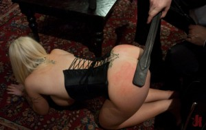 Busty blonde with a kinky corset gets her ass red from being hit with a paddle in bondage sex