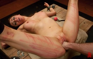 Brown-haired woman with big breasts and red marks on her ass gets her ass fisted by a man
