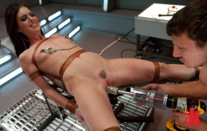 Brunette whore is tied down to a device, wears nipple clamps and tries out a fucking machine