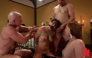 Brunette, submissive woman with a ball gag is tied up and has her pussy teased by two men